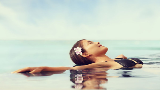 woman relaxing in an infinity pool