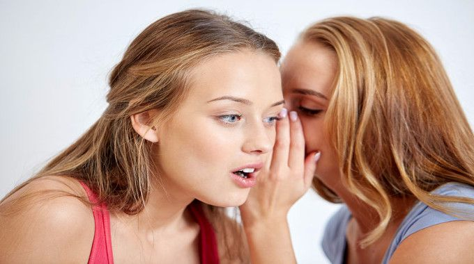 young-women-gossiping-and-whispering-to-ear-at-home-compressed