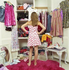 Girl (9-11) looking in wardrobe, hands on hips, rear view