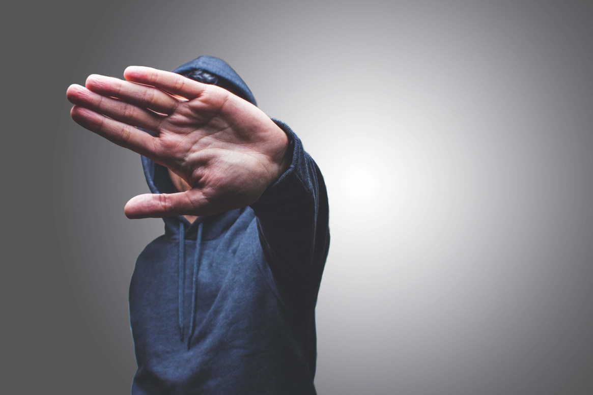 view of a man showing his hand hiding his face