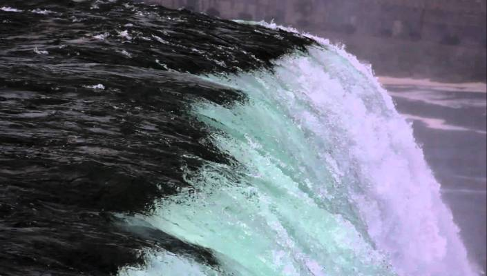 Close up side view of water cascading over waterfall