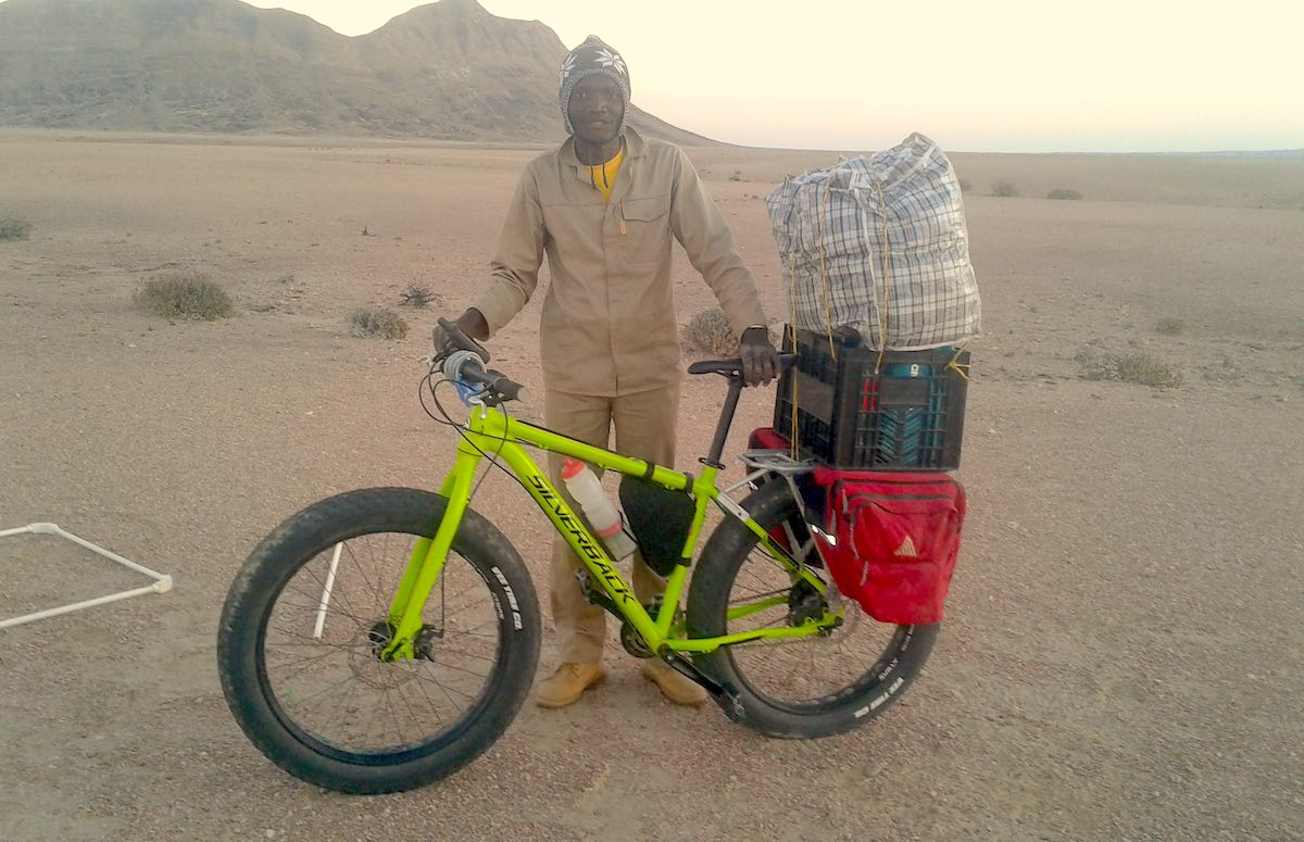 The author stands next to a lime-green fatbike loaded with supplies.