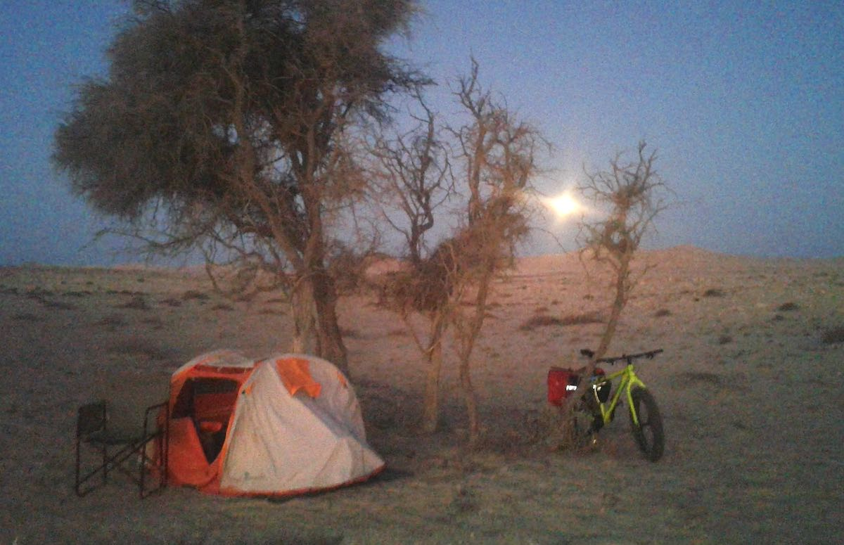 The sun rises in the background, and illuminates a lonely campsite with a single tent under an acacia tree.