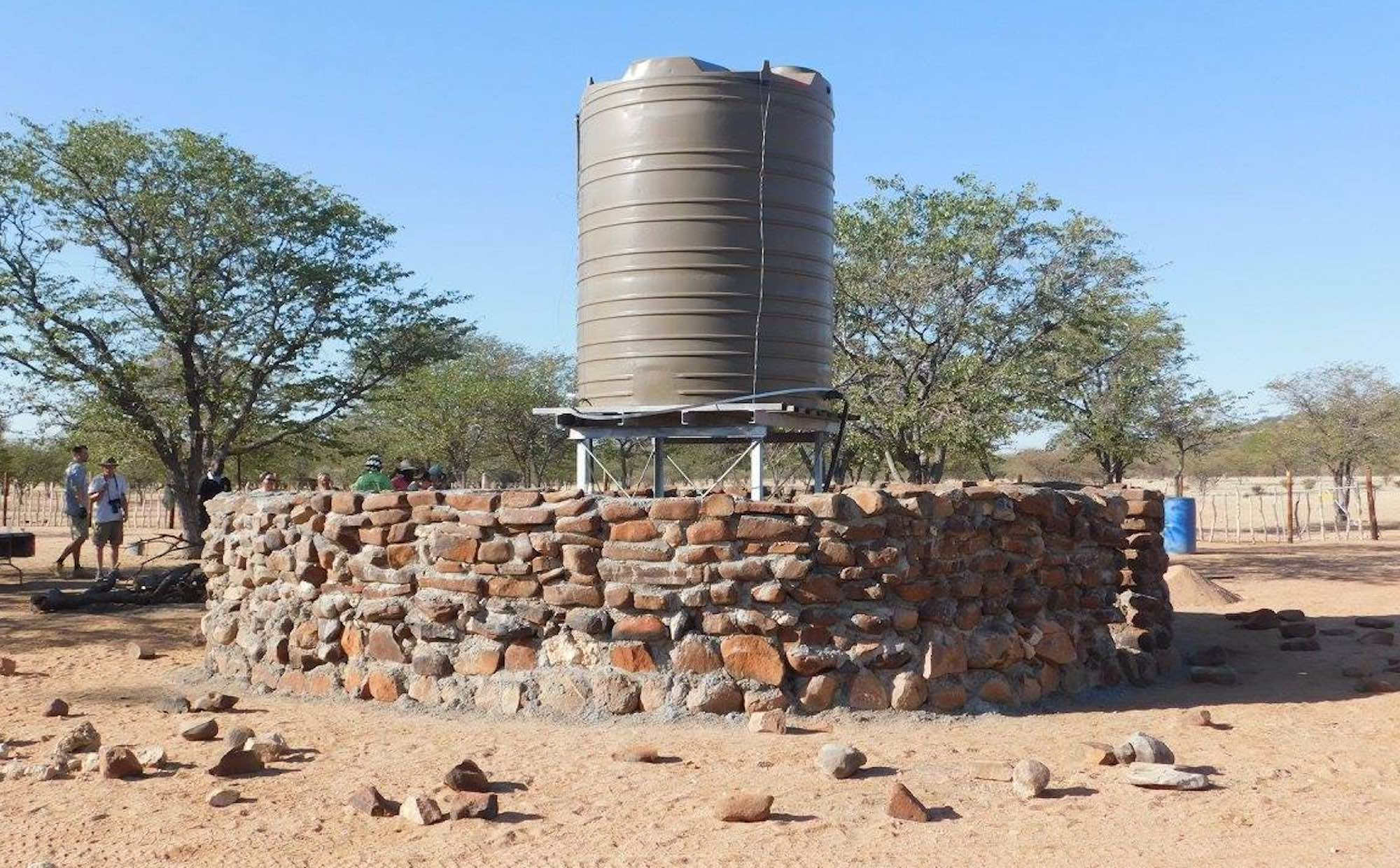 A water tank surrounded by a thick stone wall cemented together.
