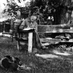 Leopold writing at his shack with dog, Flick.