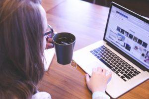 girl holding a mug browsing through the laptop