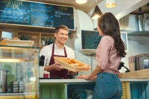 smiling baker smiles at consumer