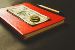 Paper bills and coins on top of a red notebook