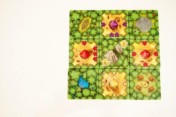 El jugador con más recolectores alrededor de un templo recibe seis monedas. El segundo, recibe tres. En este caso, el jugador rojo recibe seis y el morado dos.