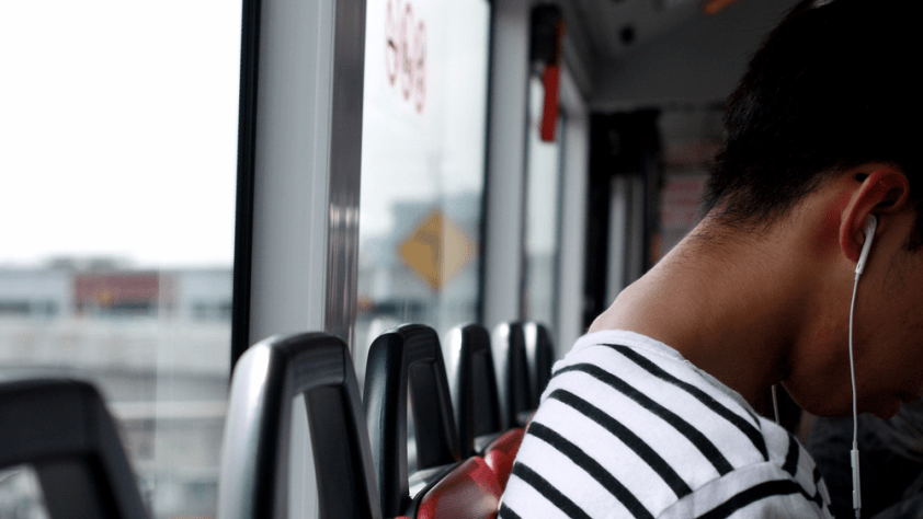 A person on a bus with their headphones in