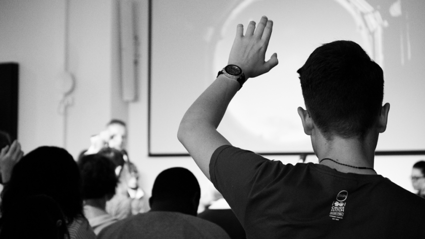 A person raising their hand to ask a question at a semeniar