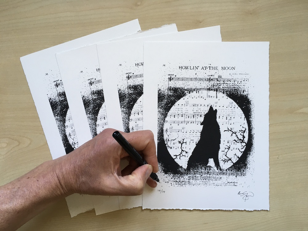 An image of the artist's hand signing a few limited edition prints. The print design is a silhouette wolf howling at the moon against a backdrop of musical notes.