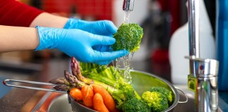 Woman washing vegetables on kitchen counter.