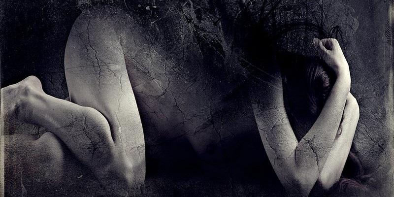 Imagem mostra uma mulher sofrendo emocionalmente. Seu corpo nu parece porcelana e tem algumas rachaduras, indicando que ela está se quebrando. Ela está deitada, com os joelhos e cotovelos apoiados no chão enquanto esconde a cabeça entre os braços. As costas, que estão viradas para cima, parecem se desfazer em meio à escuridão ao redor.