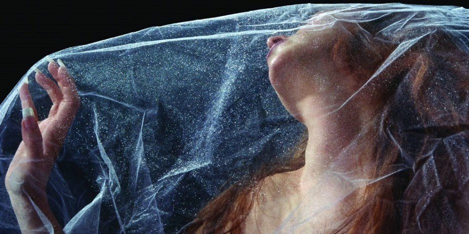 Imagem ilustra a ideia de claustrofobia. Uma mulher está presa em um véu transparente e sofre com isso.