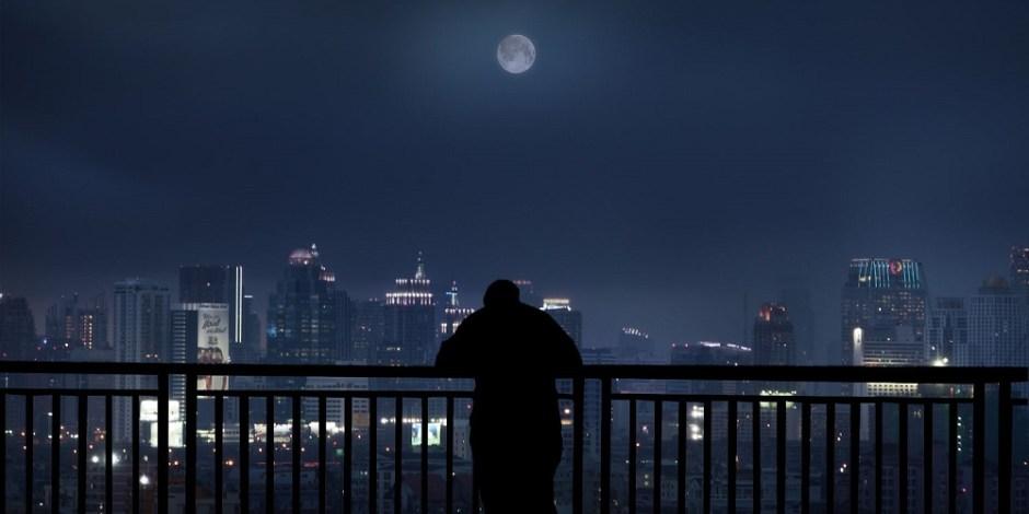 Um homem está na varanda de um apartamento no meio da noite. Ele observa a cidade abaixo enquanto a lua ilumina o céu.
