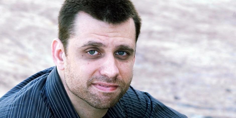 Foto do escritor Eduardo Spohr. Spohr é um homem adulto e branco, de olhos claros e cabelo escuro. A foto registra apenas o seu rosto e um pouco dos ombros. Ele olha para frente, direto para o observador.