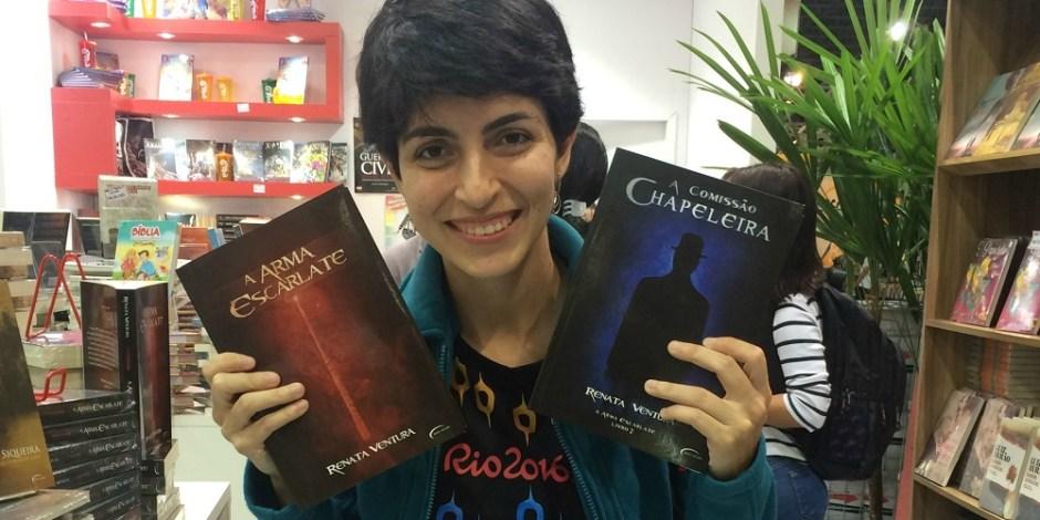 """A escritora Renata Ventura está em estande na Bienal do Livro. Ela segura em cada uma das mãos um de seus livros. Na mão direita está """"A Arma Escarlate"""". Na mão esquerda está """"A Comissão Chapeleira"""". Ao seu redor, estão vários livros."""