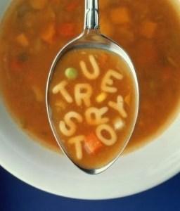 """Sopa de letras com uma colher ao centro da tela, com a palavra """"True Story"""" escritas com a sopa dentro da colher"""