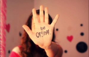 Mão com a frase be original escrita na palma