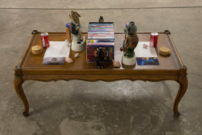 Jackie T. Kennedy and Sean Kennedy, For Lottie and Hans (2015). Coffee table, Kennedy family DVD collection, poodle bookends, Republican and Democratic candlestick holders, Meica jarred frankfurters, Coca-Cola, drawings on notebook pages, photographs taken at 23 Rat-Bell-Stresse, Frankfurt, Germany, 60318, digestive biscuits, Goethe and Schiller salt and pepper shakers, chipmunk salt and pepper shakers, ceramic pig chopstick rests, tortoise tchotchkes, and Japanese figurines. Image courtesy of the artists and JOAN, Los Angeles. Photo: Dawn Blackman.