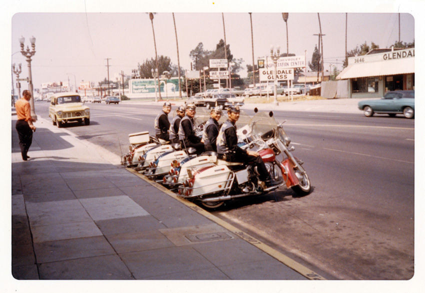 Five Blue Max Motorcycle Club members in uniform jackets and Pickelhauben helmets seated on Harley Davidson Electra Glide motorcycles at curb in Glendale, California. Circa 1970.