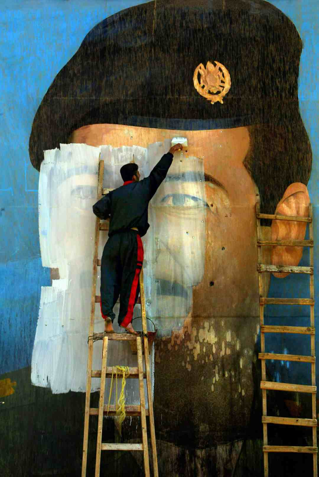 Carolyn Cole, An image of Saddam Hussein, riddled with bullet holes, is painted over by Salem Yuel. Symbols of the leader disappeared quickly throughout Baghdad soon after US troops arrived in the city and took control, Baghdad, Iraq, April 2003. © Carolyn Cole / Los Angeles Times