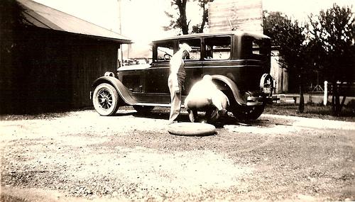 vintage men changing flat tire 1920s