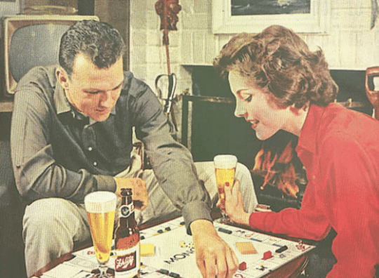 vintage man woman couple drinking beer playing monopoly