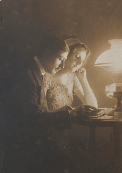 vintage 1800s couple reading together oil lamp