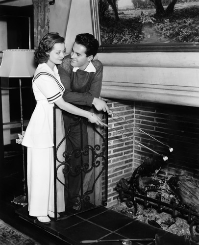 vintage couple roasting marshmallows in fireplace