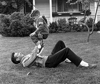 The Lost Art Of Roughhousing: Why Roughhousing Makes Kids Awesome, horseplay, wrestling, wrasling, being a dad, chasing, horsing around, laughing, monkey, Brett and Kate McKay, Art of Manliness, throw down, bad rap, parents, safety, preventing ADHD, rambunctious play, schools eliminated recess, getting hurt, violent behavior, banned recess, slapping, teachers, The Art of Roughhousing,Anthony DeBenedet, Larry Cohen, impulsive, benefits, smartkids, emotionally intelligent, lovable and likable, ethical, physically fit, joyful, baby suplex, resilience, bounce back, failures, happier adults, adaptable, full potential, children, homeschool, homeschooling,Marc Bekoff, book,Wild Justice, child's brain, cerebral cortex, connection between neurons, rewires brain, roughhouse, work, play, learn from mistakes, playtime, fun, safe place, victory, learn from mistakes, deal with pain, discomfort, bumps and bruises, scrapes, boo boos, distraction, humor, toddler Einstein, keep trying, neuroscientists, rough and tumble, neurotrophic factor,memory, logic, higher learning–skills, academic success, moms, afraid, social intelligence, research, Dr. Stuart Brown, expert on play, social mastery, play fight, poor self control, aggression, social clues, taking turns, cooperation, negotiation, goal, taking turns, back-and forth, role reversal,vintage dad roughhousing with boy outside lawn