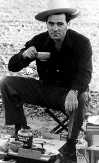 Louis L'Amour sitting in chair drinking coffee cowboy hat
