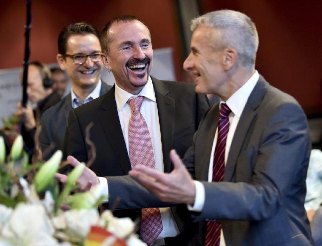 Karl Kreile, center, and Bodo Mende, right, laugh in Berlin