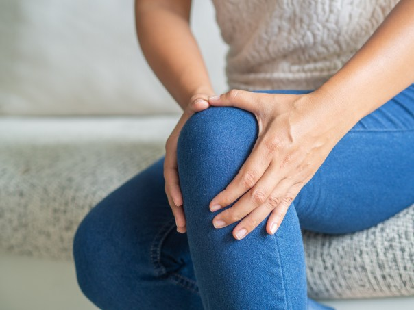 Closeup young woman sitting on sofa and feeling knee pain and she massage her knee. Healthcare and medical concept.
