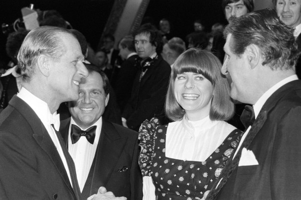 Pam Ayres and comic magician Tommy Cooper talking to the Duke of Edinburgh Silver Jubilee Royal Variety Gala at the London Palladium with Her Majesty the Queen in 1977 (PA)