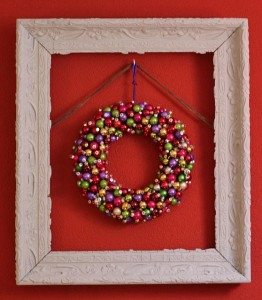 christmas wreath in a frame on a red wall