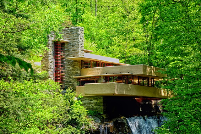 Frank Lloyd Wright's Fallingwater House, a Modern three-story home with a stone chimney that is surrounded by trees.