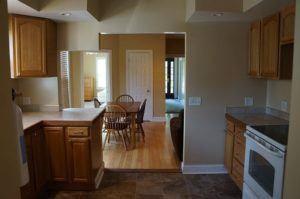 A dimly lit kitchen with tile floors, wood cabinets, and laminate countertops looking out onto a dimly lit dining area.
