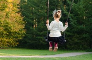 Young girl swinging in the park.