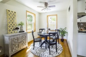 Bright dining room with hardwood floor, small black table, modern decor, and a ceiling fan.
