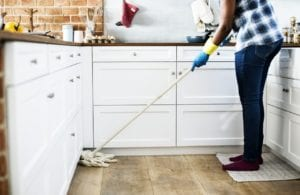 A woman mopping her kitchen floor.