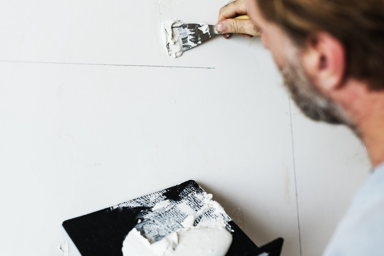 A man patching up a wall.