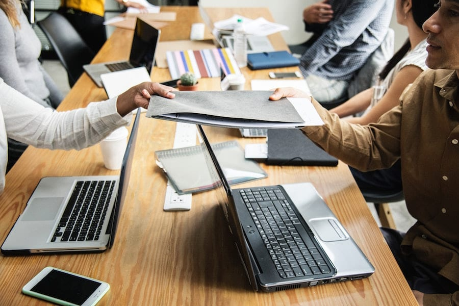 People with laptop exchanging a folder.