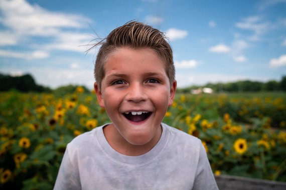 boy standing in a field of sunflowers smiling
