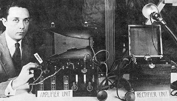 "A historical black-and-white photo shows a man in a suit with equipment labeled ""Amplifier Unit"" and ""Rectifier Unit."""