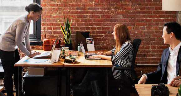 Image: Small office scene of two women and a man working at their desks.