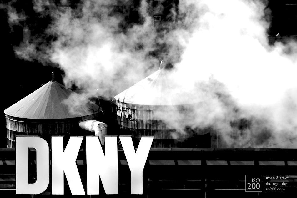 Rooftop DKNY sign, with water towers and steam. Classic Manhattan skyline.