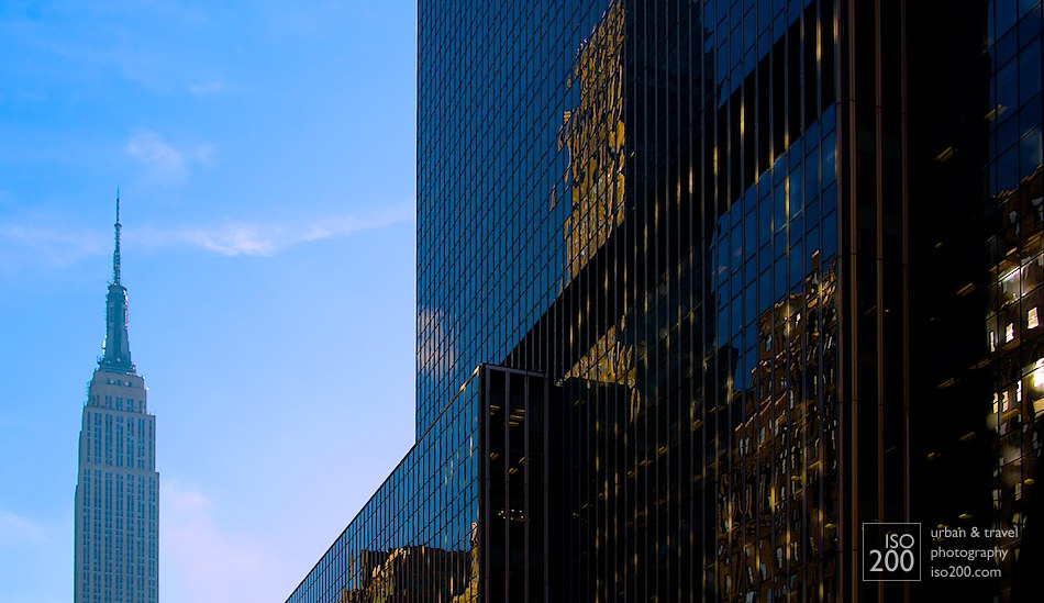 The Empire State Building in downtown Manhattan, juxtaposed against reflections from other skyscrapers against black mirrored glass, Manhattan, New York.