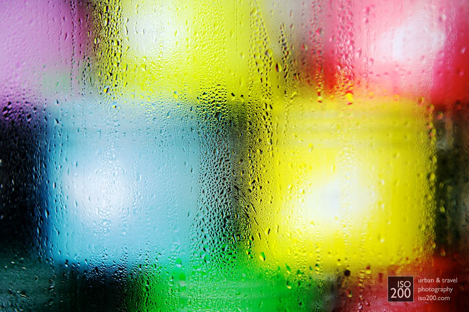 Brightly coloured candles seen through a mottled glass window, Copenhagen.